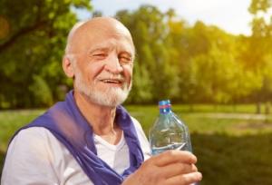 Durstiger Senior trinkt Wasser im Sommer aus einer Flasche in der Natur